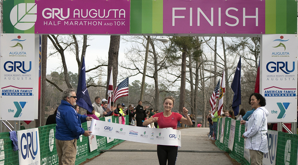 Aubrey Armento breaks through finish line banner with arms raised